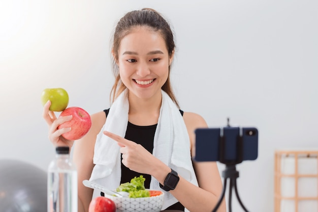 Beautiful asian woman healthy blogger is showing apple fruite and clean diet food. Premium Photo