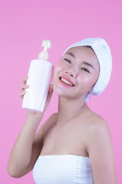 Beautiful asian woman holding a bottle of product on a pink background. Free Photo