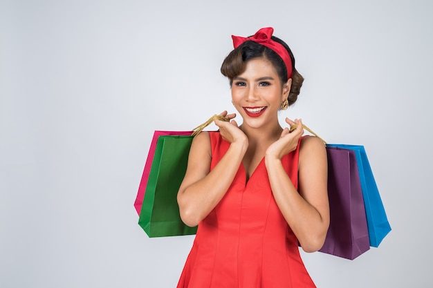 Beautiful asian woman holding colored shopping bags Free Photo