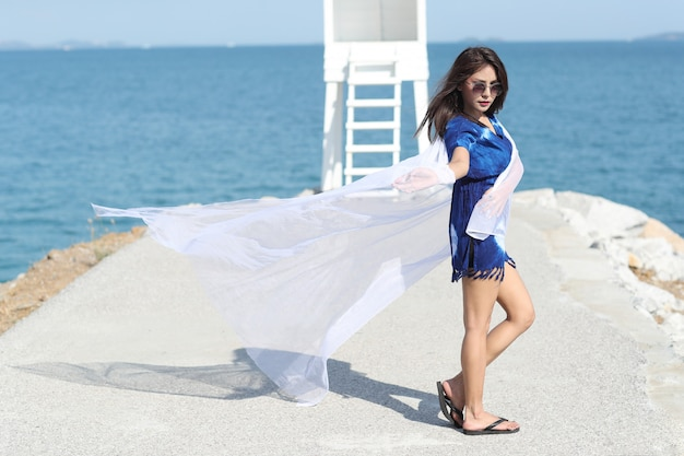 Beautiful asian woman holding white cloth and enjoy holiday vacation on the beach Premium Photo
