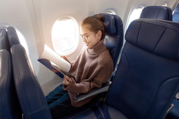 Beautiful asian woman is reading magazine in airplane Premium Photo