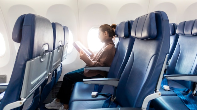 Beautiful asian woman is reading magazine in airplane Premium Photo