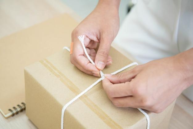 Красивая азиатская женщина пакуя почтовый пакет на таблице, онлайн-покупках и электронной коммерции в малом стартапе. Premium Фотографии
