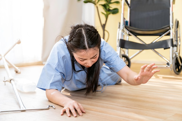 Beautiful asian woman patient accident falling down and crawling for help in hospital room. Premium Photo