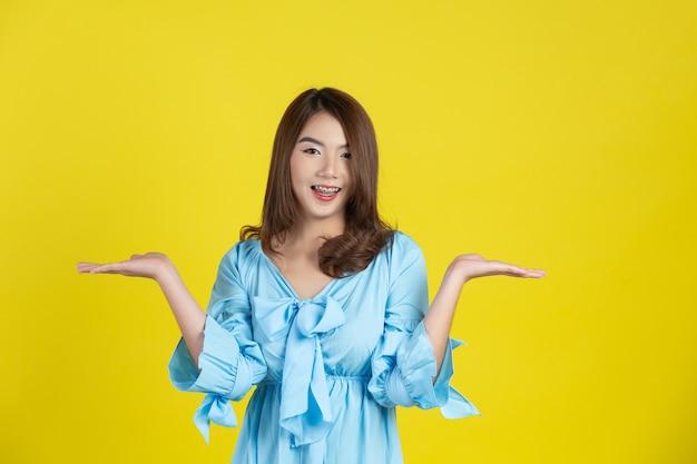 Bella donna asiatica che indica la mano per svuotare lo spazio da parte sulla parete gialla Foto Gratuite