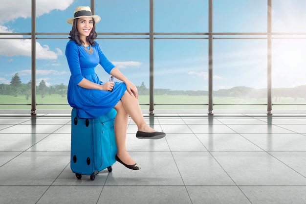 Beautiful asian woman sitting on suitcase while waiting for departure airplane Premium Photo