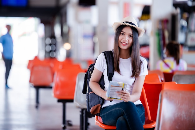 Beautiful asian woman  smiling with map and bag at bus station Free Photo