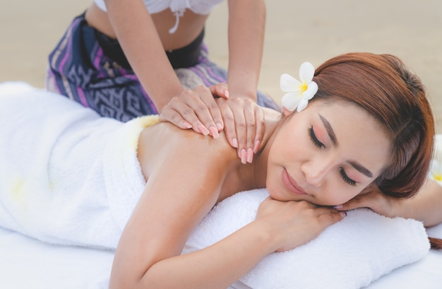 Beautiful asian woman spa body massage treatement oil on the beach Premium Photo