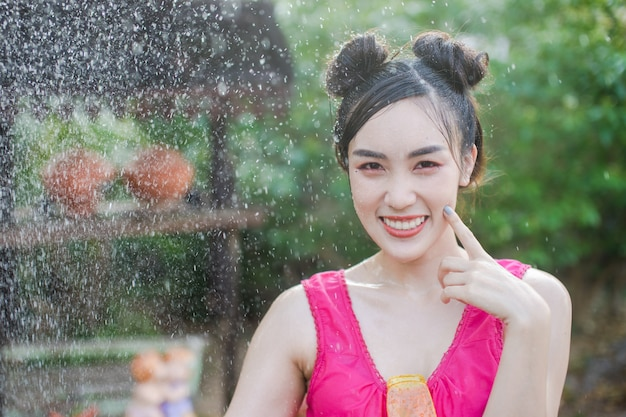 Beautiful asian woman in traditional costume of thailand playing water in songkran festiva Premium Photo