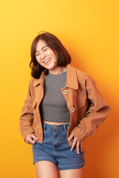Beautiful asian woman university student happy on yellow wall Premium Photo