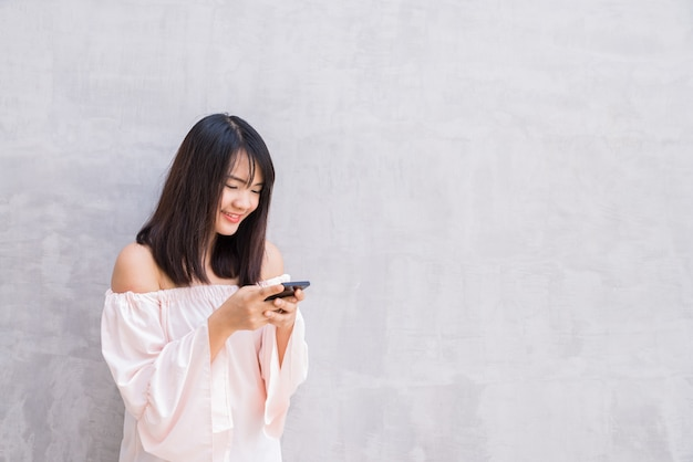 Beautiful asian woman using cellphone, over concrete wall Premium Photo