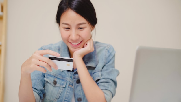 Beautiful asian woman using laptop buying online shopping by credit card while wear casual sitting on desk in living room at home. Free Photo