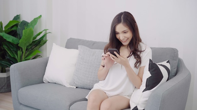 Beautiful asian woman using smartphone while lying on the couch in her living room. Free Photo