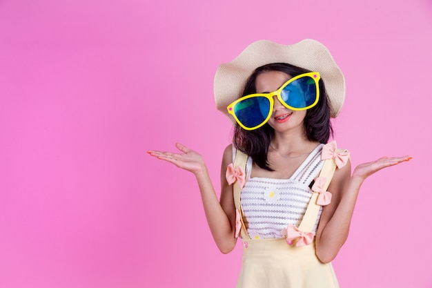 A beautiful asian woman wearing a hat and large glasses with a pink . Free Photo
