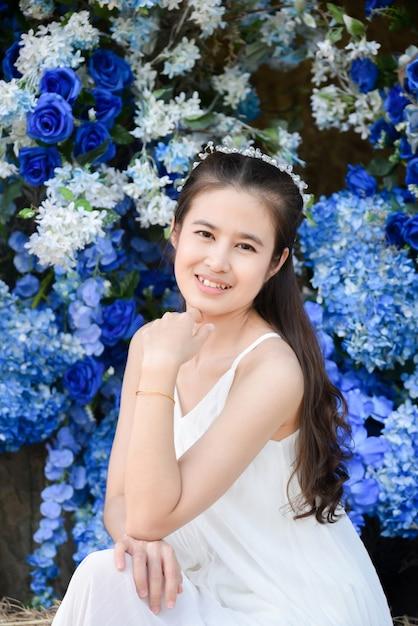 파란색 꽃 앞에 앉아 흰 드레스를 입고 아름 다운 아시아 여자. 프리미엄 사진