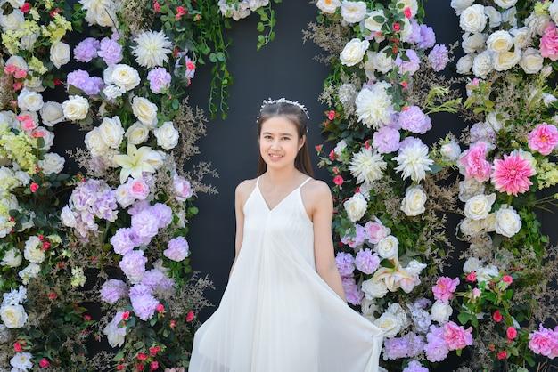 꽃과 검은 색 배경 앞에 서있는 흰색 드레스를 입고 아름 다운 아시아 여자. 프리미엄 사진
