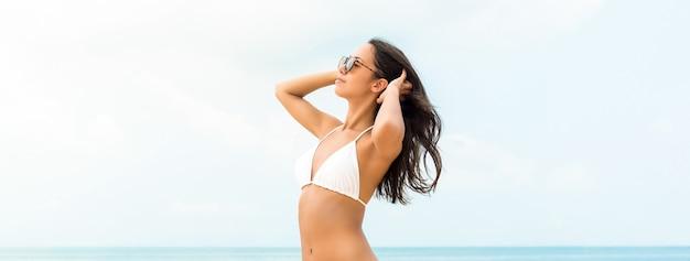 Beautiful asian woman wearing white swimsuit on summer beach banner background Premium Photo