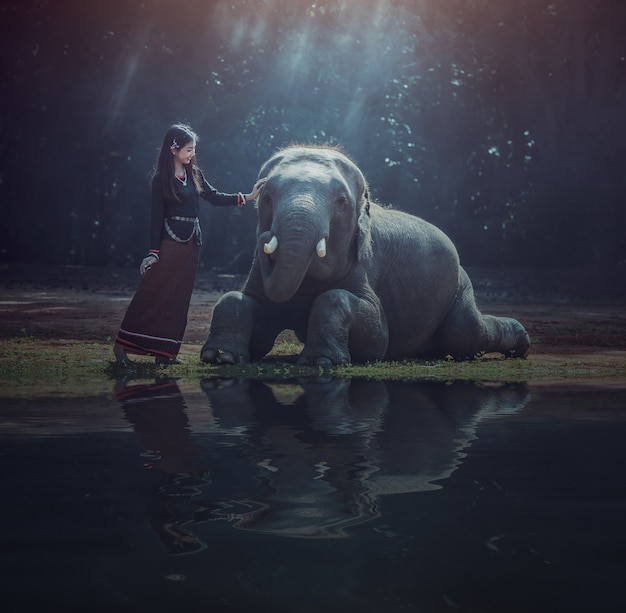 Beautiful asian woman wears thai dress with her elephant, surin, countryside of thailand Premium Photo