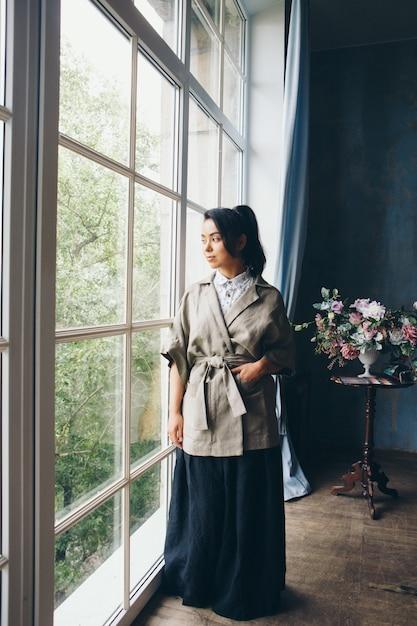 Красивая азиатская женщина с прической в японском стиле и кимоно у окна на фоне домашнего интерьера Premium Фотографии