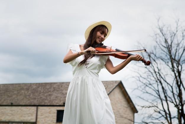 Красивая азиатская женщина с длинными волосами играет на скрипке Premium Фотографии