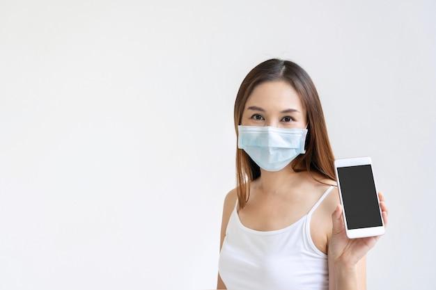 白い背景の上のコピースペースのスマートフォンを保持している医療フェイスマスクを持つ美しいアジアの女性。 Premium写真