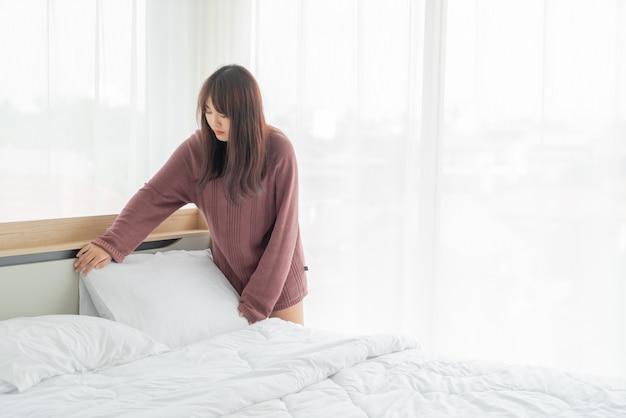 Красивые азиатские женщины заправляют кровать в комнате с белой чистой простыней Premium Фотографии