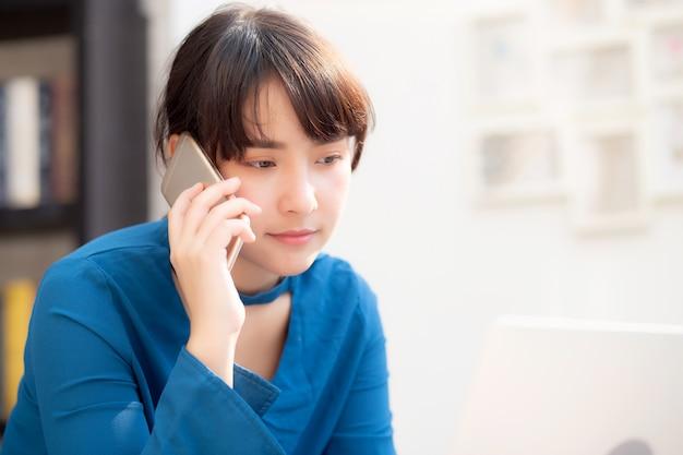 Красивая азиатская молодая коммерсантка возбужденная и довольная работа успеха с компьтер-книжкой, девушкой принимая мобильный смартфон Premium Фотографии