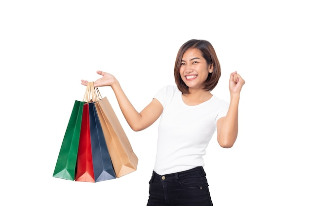 Красивая азиатская молодая женщина улыбается, держа изолированные сумки для покупок Premium Фотографии