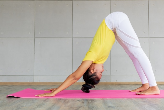 Beautiful asian young woman wearing sportswear practicing yoga in studio,natural light.concept : yoga poses for beginner. Premium Photo