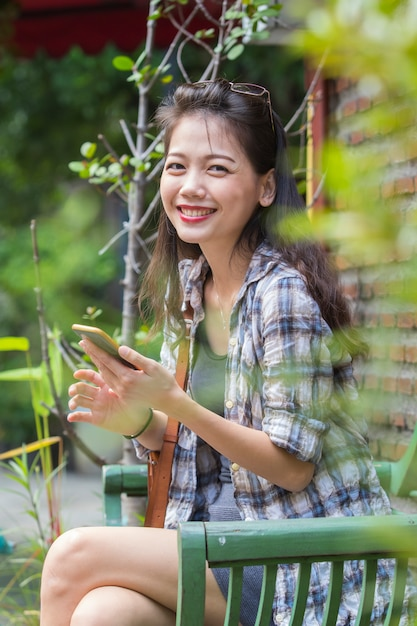 Beautiful asian younger woman laughing with happiness emotion reading smart phone Premium Photo