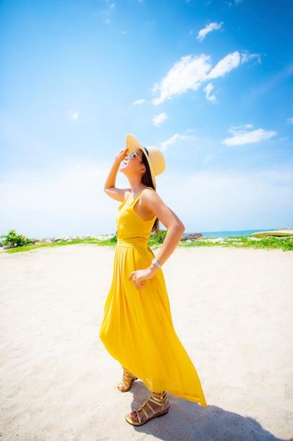 Beautiful asian younger woman wearing  yellow dress relaxing on summer vacaiton beach Premium Photo