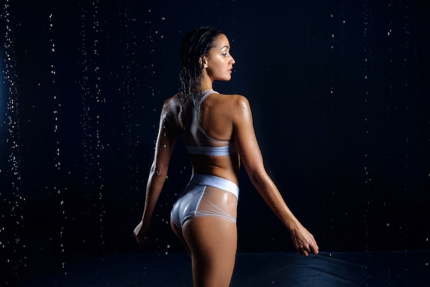 Beautiful athletic caucasian girl with a perfect figure is standing under the water. Premium Photo