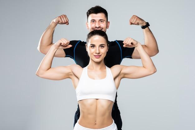 美しい運動カップルは灰色の背景に上腕二頭筋を表示します。 Premium写真