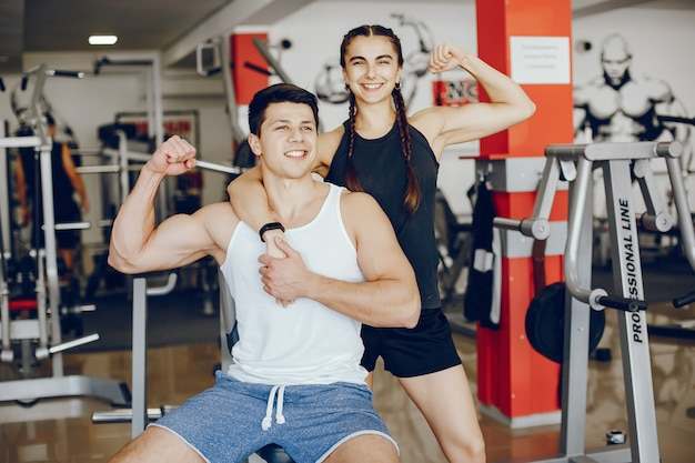 A beautiful and athletic sportswear girl training in the gym with her boyfriend Free Photo