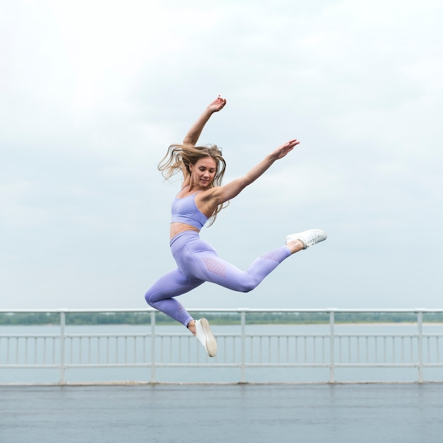 Beautiful athletic woman jumping long shot Free Photo
