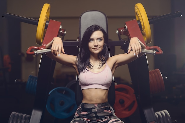 Beautiful athletic young woman working out in gym Premium Photo