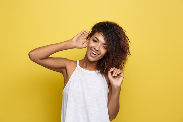 Beautiful attractive african american woman posting play with her curly afro hair. yellow studio background. copy space. Free Photo