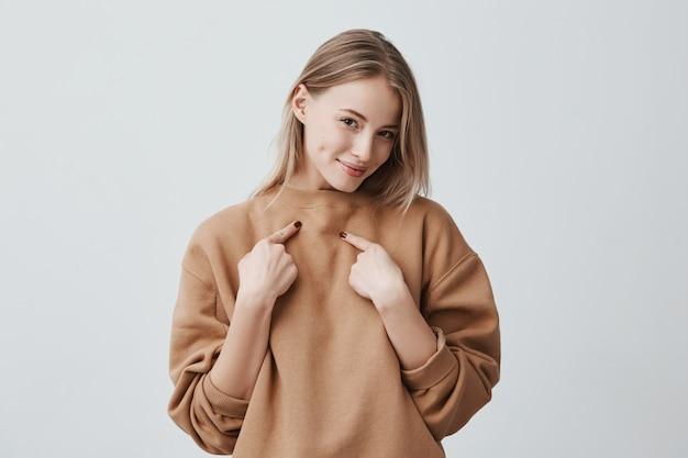 笑みを浮かべて、人差し指で自分を指して、ベージュの長袖のセーターを着て、肯定的な感情と感情を表現する美しい魅力的なブロンドの女性。 無料写真