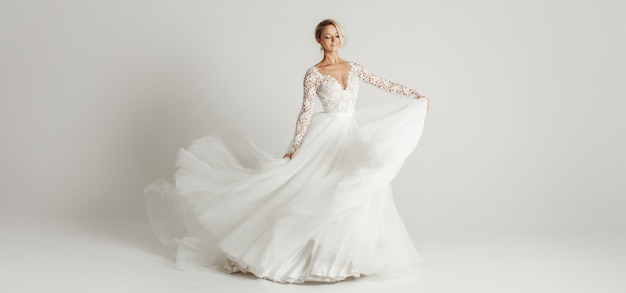 Beautiful attractive bride in wedding dress with long full skirt Premium Photo