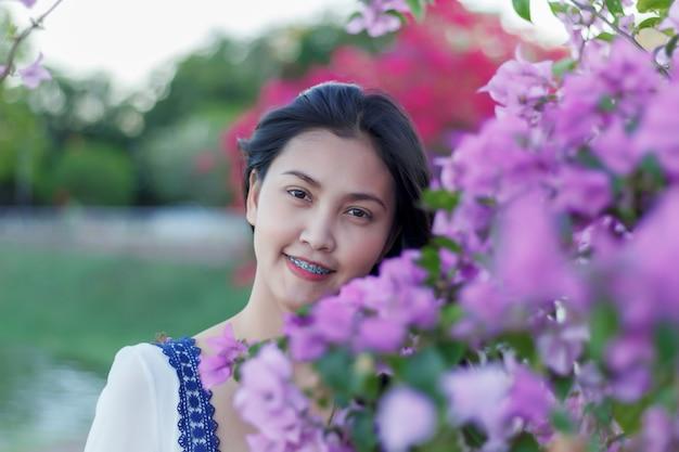 公園でカラフルな花を持つ美しい魅力的な女の子 Premium写真