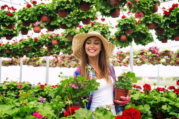 鉢植えの花を保持し、植物をチェックして温室を歩く帽子を持つ美しい魅力的な女性の花屋 無料写真