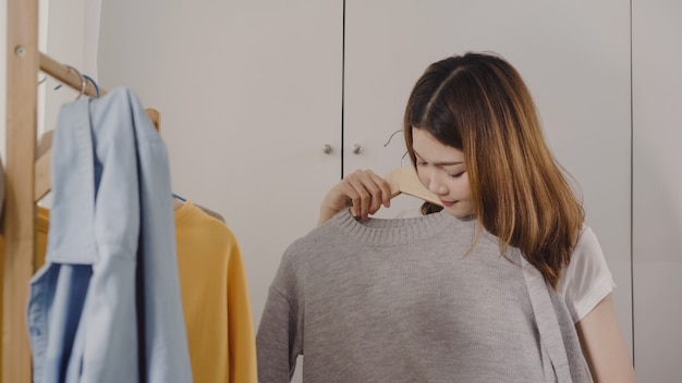 Beautiful attractive young asian woman choosing her fashion outfit clothes in closet at home Free Photo