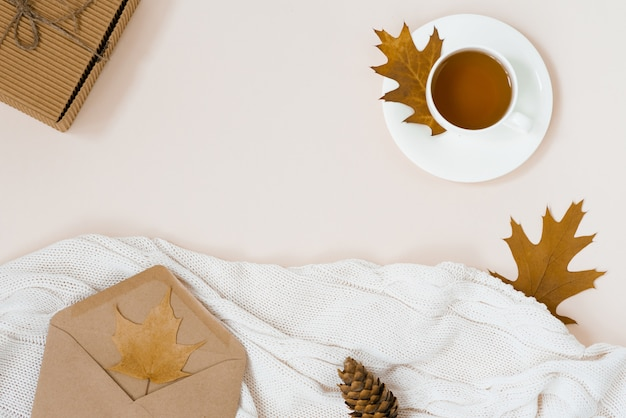 Beautiful autumn composition with a cup of tea. autumn leaves, kraft gift box, an envelope and a knitted blanket Premium Photo