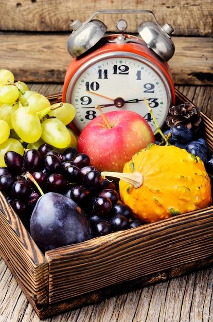 Beautiful autumn harvest and clock Premium Photo