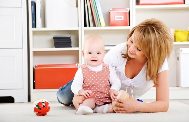室内で幸せな母とおもちゃで遊んで美しい赤ちゃん 無料写真