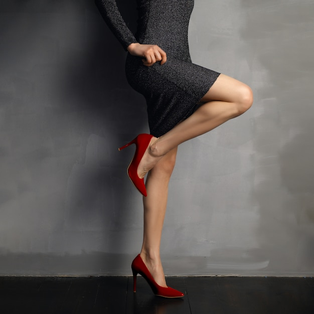 Beautiful bare female legs in red patent leather shoes, bent knee, view in profile. Premium Photo