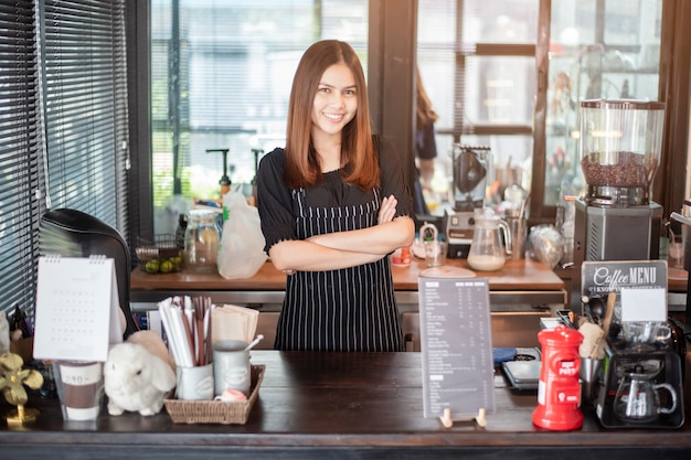 Beautiful barista is smiling  in her coffee shop Premium Photo