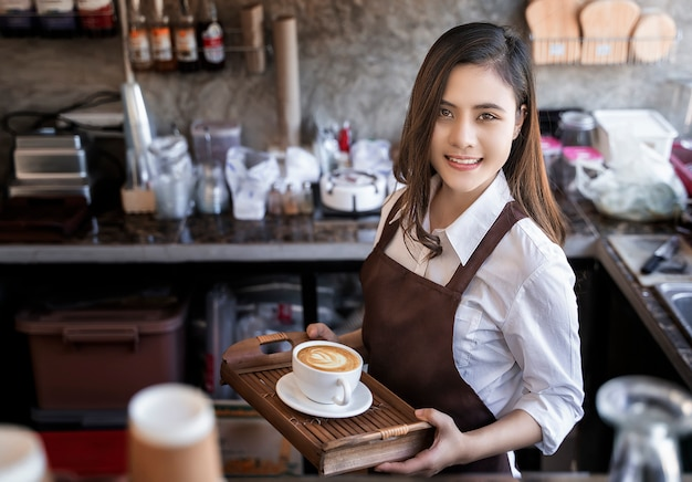 Beautiful barista wearing brown apron holding hot coffee cup served to customer with smili Premium Photo