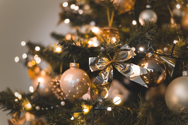 Beautiful baubles and string lights hanging on a christmas tree Free Photo