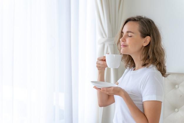 美しい美女かわいい女の子は朝のコーヒーを飲んで幸せを感じます 無料写真